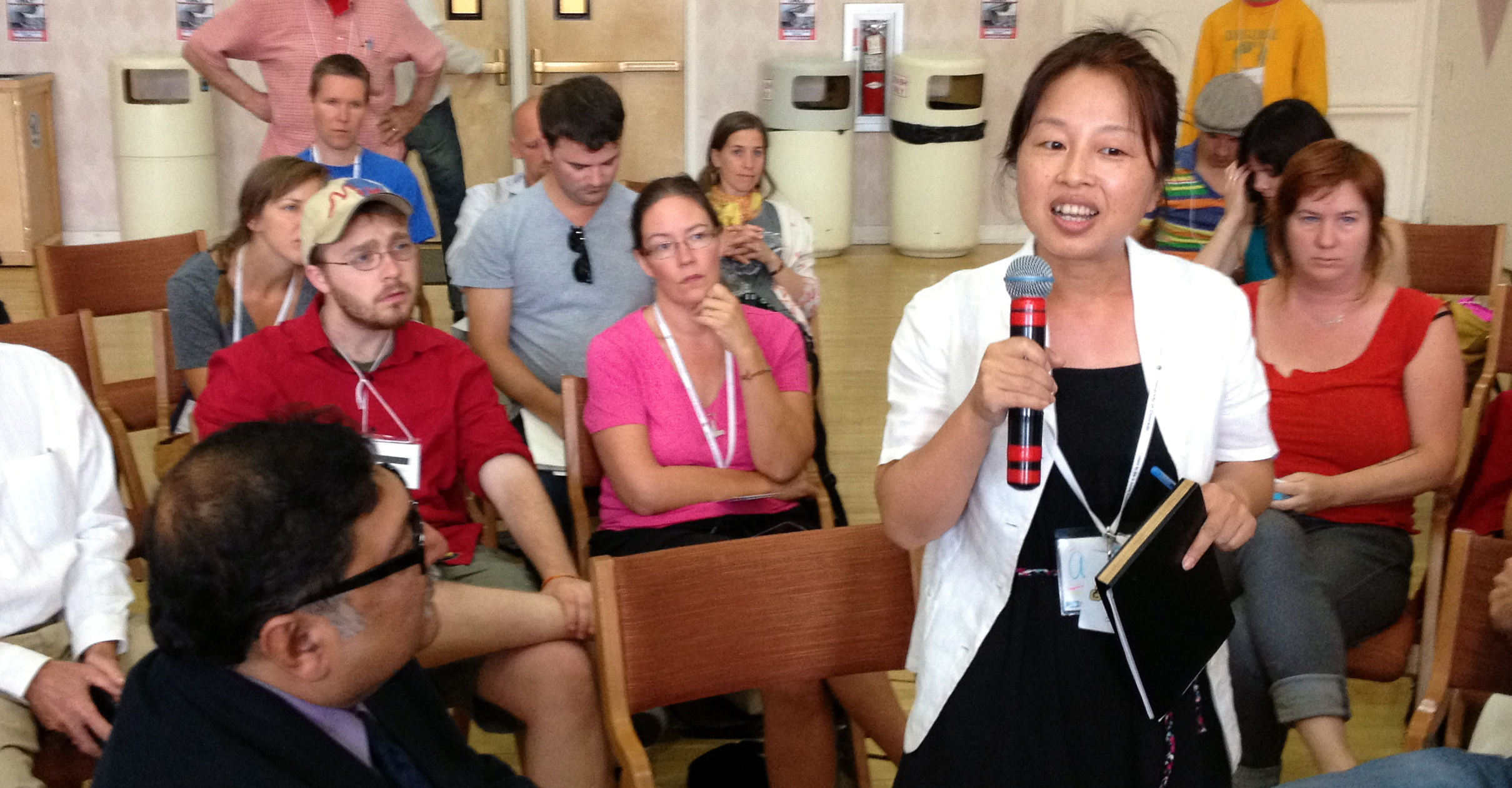 Ann Qiu speaks at the 2013 International Democratic Education Conference as Sugata Mitra and attendees listen.